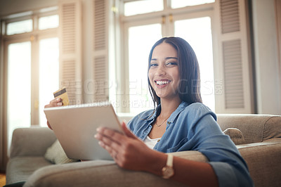 Buy stock photo Portrait of a young woman holding holding her credit card while browsing on a digital tablet