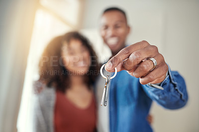 Buy stock photo Defocused shot of a young couple holding the keys to their new home