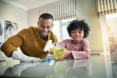 Buy stock photo Shot of a young boy helping his father to clean the kitchen