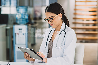 Buy stock photo Cropped shot of an attractive young doctor working on a tablet while sitting in her office during the day
