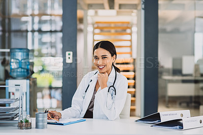 Buy stock photo Cropped portrait of an attractive young doctor sitting and smiling while in her office during the day