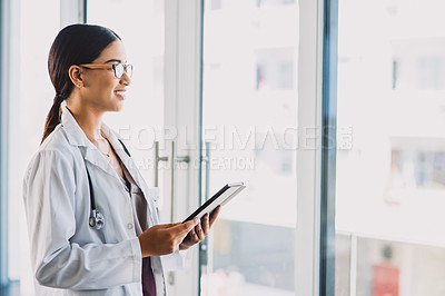 Buy stock photo Cropped shot of an attractive young doctor working on a tablet while standing in her office during the day