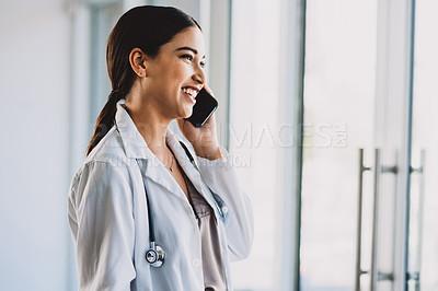 Buy stock photo Cropped shot of an attractive young doctor making a phone call while standing in her office during the day