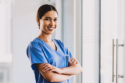 Buy stock photo Cropped portrait of an attractive young nurse standing with her arms folded and smiling while in her office
