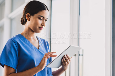 Buy stock photo Cropped shot of an attractive young nurse using a tablet while standing in her office during the day