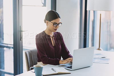 Buy stock photo Shot of a young businesswoman working on a laptop in an office