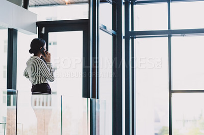Buy stock photo Rearview shot of a young businesswoman talking on a cellphone in an office