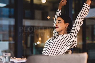 Buy stock photo Shot of a young businesswoman stretching her arms while working in an office at night