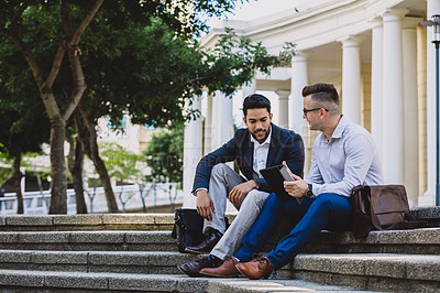 Buy stock photo Shot of two young businessmen sitting on steps and using a digital tablet in the city