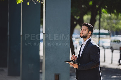 Buy stock photo Shot of a young businessman using a digital tablet in the city
