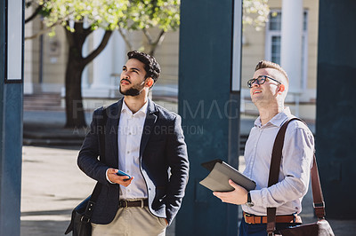 Buy stock photo Shot of two young businessmen using a digital tablet while walking through the the city