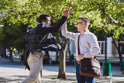 Buy stock photo Shot of two young businessmen giving each other a high five in the city