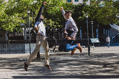 Buy stock photo Shot of two young businessmen cheering in the city