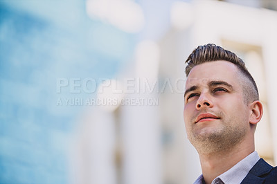 Buy stock photo Shot of a confident young businessman looking thoughtful in the city