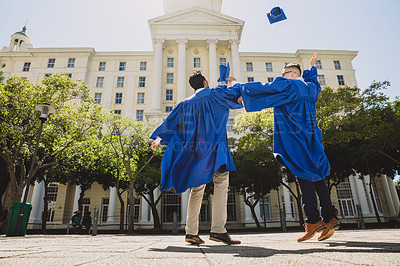 Buy stock photo Shot of two young men celebrating by throwing their hats in the air on graduation day