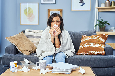 Buy stock photo Shot of an attractive young woman blowing her nose with a tissue in her living room at home