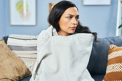 Buy stock photo Shot of an attractive young woman covering herself with a blanket and looking upset in her living room home
