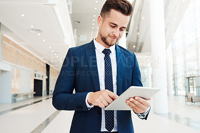 Buy stock photo Cropped shot of a handsome young businessman standing and using a tablet while in the office during the day