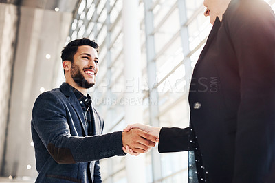 Buy stock photo Cropped shot of a handsome young businessman shaking hands with his mature colleague while in the office