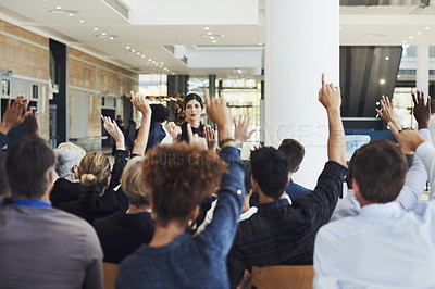 Buy stock photo Shot of a group of businesspeople raising their hands to ask questions during a conference