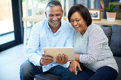 Buy stock photo Cropped shot of a mature couple using a digital tablet while relaxing at home