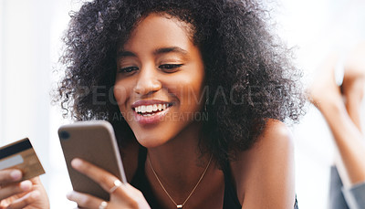 Buy stock photo Shot of a young woman using a credit card and smartphone