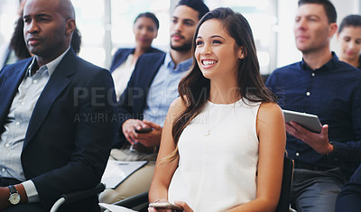 Buy stock photo Shot of a happy young businesswoman sitting in the audience of a business conference
