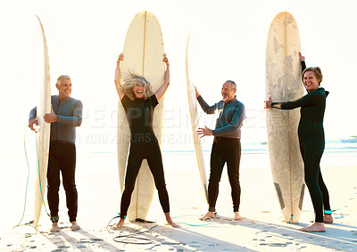 Buy stock photo Full length shot of a group of happy senior people standing on the beach with their surfboards during the day