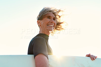 Buy stock photo Cropped shot of a happy senior woman holding her surfboard and looking away while on the beach during the day