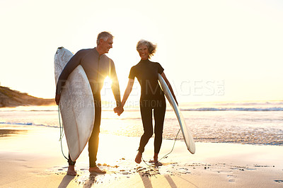 Buy stock photo Full length portrait of an affectionate senior couple carrying their surfboards while walking along the beach at sunset