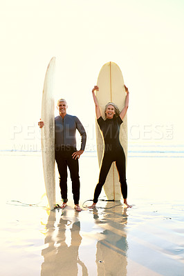 Buy stock photo Full length portrait of a happy senior couple standing and posing with their surfboards while on the beach