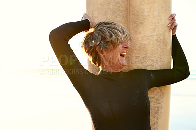 Buy stock photo Cropped shot of a happy senior woman standing with her surfboard and laughing while on the beach during the day