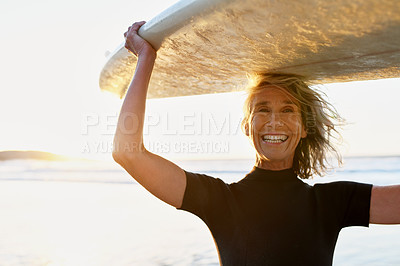 Buy stock photo Cropped portrait of a happy senior woman carrying her surfboard over her head after surfing during the day