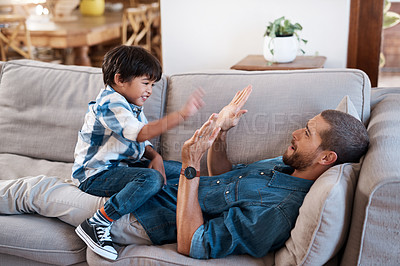 Buy stock photo Shot of a man spending quality time with his young son at home
