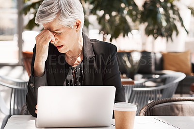Buy stock photo Shot of a stressed out mature businesswoman using a laptop while sitting in an airport cafe