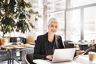 Buy stock photo Portrait of a mature businesswoman using a laptop while sitting in an airport cafe