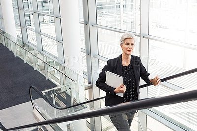 Buy stock photo Shot of a mature businesswoman traveling on an escalator in an airport