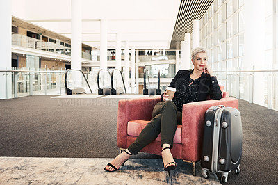 Buy stock photo Shot of a mature businesswoman sitting on a chair in an airport lounge