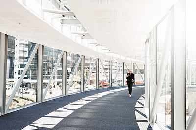 Buy stock photo Shot of a mature businesswoman using a smartphone while walking through a convention centre