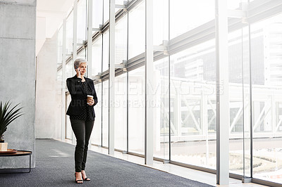 Buy stock photo Shot of a mature businesswoman using a smartphone in a convention centre