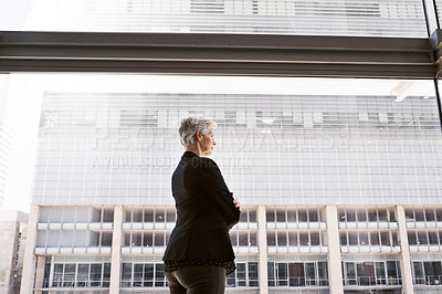 Buy stock photo Shot of a confident mature businesswoman looking thoughtfully out of a window in a convention centre