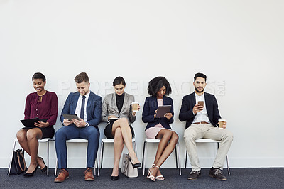 Buy stock photo Studio shot of a group of young businesspeople using wireless technology while sitting in line against a white background