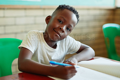Buy stock photo Shot of a young boy doing schoolwork in a classroom