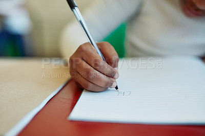 Buy stock photo Cropped shot of a young girl writing in a notepad at her classroom desk