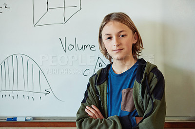 Buy stock photo Shot of a confident young boy standing in front of a board with mathematics symbols on it in a classroom