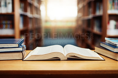 Buy stock photo Shot of an open book on a table in a library