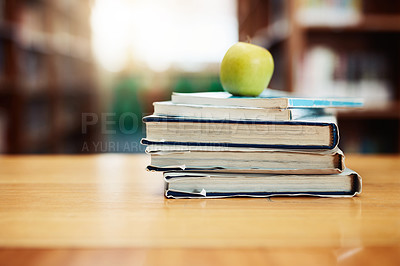 Buy stock photo Shot of a stack of books and apple on a table in a library
