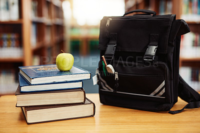 Buy stock photo Shot of a stack of books, an apple and a schoolbag on a table in a library
