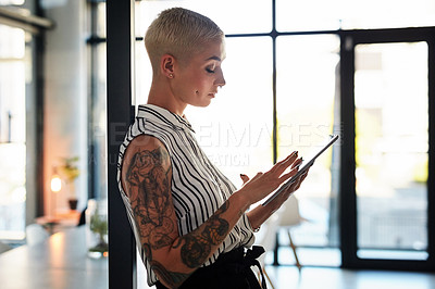 Buy stock photo Shot of an attractive young businesswoman using her digital tablet while working late in her office