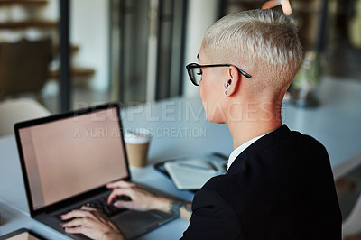 Buy stock photo Shot of an attractive businesswoman using a laptop while working late in her office